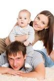 Счастливая семья отдыхая на ковре стоковые фото