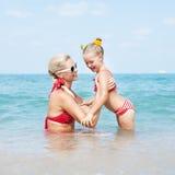 Счастливая семья отдыхая на пляже в лете Стоковое Изображение