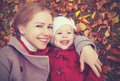 Счастливая семья: дочь матери и ребенка маленькая играет прижиматься на осени Стоковое Изображение RF