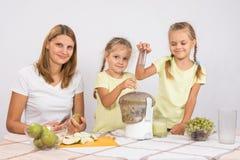 Счастливая семья подготавливает свеже сжиманный сок в juicer Стоковые Фото