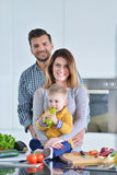 Счастливая семья подготавливая овощи совместно дома в кухне Стоковая Фотография
