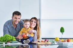 Счастливая семья подготавливая овощи совместно дома в кухне Стоковые Изображения