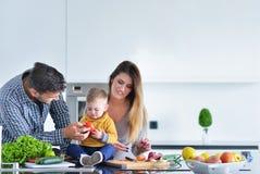 Счастливая семья подготавливая овощи совместно дома в кухне Стоковые Фото