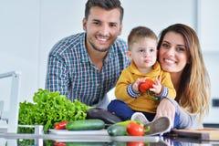 Счастливая семья подготавливая овощи совместно дома в кухне Стоковое Изображение RF