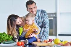 Счастливая семья подготавливая овощи совместно дома в кухне Стоковые Фотографии RF