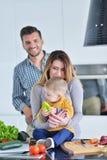Счастливая семья подготавливая овощи совместно дома в кухне Стоковое Изображение