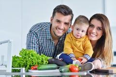 Счастливая семья подготавливая овощи совместно дома в кухне Стоковые Изображения RF