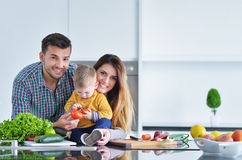 Счастливая семья подготавливая овощи совместно дома в кухне Стоковая Фотография RF