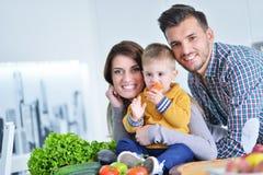 Счастливая семья подготавливая овощи совместно дома в кухне Стоковое Фото