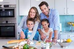 Счастливая семья подготавливая овощи совместно Стоковая Фотография