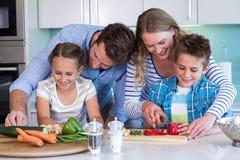 Счастливая семья подготавливая овощи совместно Стоковое Изображение RF