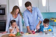Счастливая семья подготавливая овощи совместно Стоковые Фотографии RF