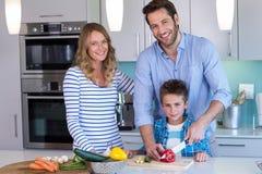 Счастливая семья подготавливая овощи совместно Стоковые Изображения