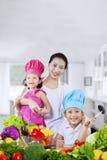 Счастливая семья подготавливая свежие овощи Стоковое фото RF