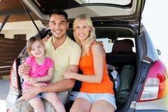 Счастливая семья при автомобиль хэтчбека дома паркуя Стоковые Фотографии RF