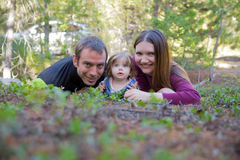 Счастливая семья при девушка малыша лежа на том основании в лесе Стоковые Изображения
