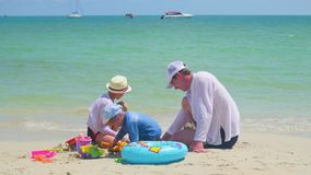 Счастливая семья при дети играя на песчаном пляже с игрушками Тропический остров, на горячий день сток-видео