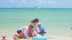 Счастливая семья при дети и собака играя на песчаном пляже с игрушками Тропический остров, на горячий день видеоматериал