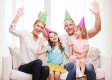 Счастливая семья при 2 дет в шляпах празднуя Стоковое Фото