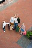 Счастливая семья при 2 дет держа бумажные сумки и усмехаясь на камере Стоковые Изображения