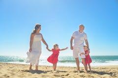 Счастливая семья при 2 дет держа руки на пляже Стоковые Изображения RF