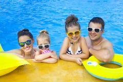 Счастливая семья при 2 дет имея потеху в бассейне Стоковые Изображения RF
