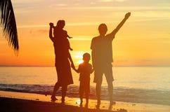 Счастливая семья при 2 дет имея потеху на заходе солнца Стоковые Фотографии RF
