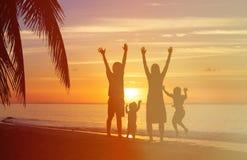 Счастливая семья при 2 дет имея потеху на заходе солнца Стоковые Изображения