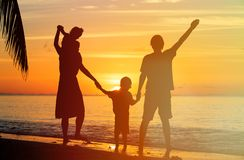 Счастливая семья при 2 дет имея потеху на заходе солнца Стоковое Изображение RF