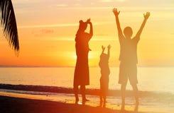 Счастливая семья при 2 дет имея потеху на заходе солнца Стоковая Фотография