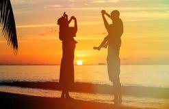 Счастливая семья при 2 дет имея потеху на заходе солнца Стоковые Изображения RF
