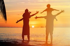 Счастливая семья при 2 дет имея потеху на заходе солнца Стоковое фото RF