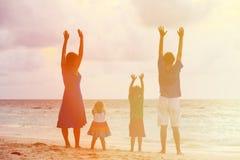 Счастливая семья при 2 дет имея потеху на заходе солнца Стоковое Изображение
