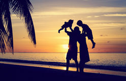 Счастливая семья при 2 дет имея потеху на заходе солнца Стоковая Фотография RF