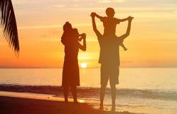 Счастливая семья при 2 дет имея потеху на пляже захода солнца Стоковая Фотография RF
