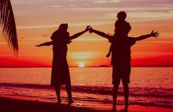 Счастливая семья при 2 дет имея потеху на пляже захода солнца Стоковая Фотография