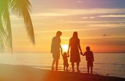 Счастливая семья при 2 дет идя на пляж захода солнца Стоковое фото RF