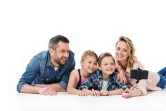 Счастливая семья при 2 дет принимая selfie с smartphone Стоковое фото RF