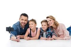 Счастливая семья при 2 дет принимая selfie с smartphone Стоковые Фотографии RF