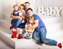 Счастливая семья при 3 дет сидя на поле живущей комнаты дома Стоковое фото RF