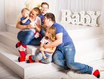 Счастливая семья при 3 дет сидя на поле живущей комнаты дома Стоковое Изображение RF