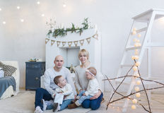 Счастливая семья при 2 дет сидя на поле дома Стоковые Фото
