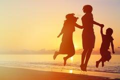 Счастливая семья при 2 дет скача на заход солнца Стоковая Фотография