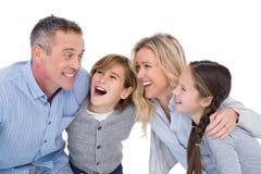Счастливая семья при 2 дет усмехаясь и обнимая Стоковое Изображение RF