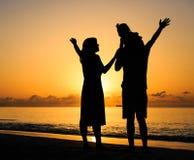Счастливая семья при ребенк имея потеху на пляже захода солнца Стоковая Фотография
