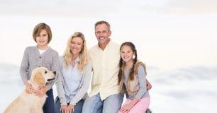 Счастливая семья при собака распологая против яркой предпосылки Стоковое Фото