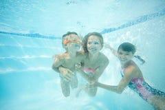 Счастливая семья плавая под водой Мать, сын и дочь имея иметь потеху в бассейне Стоковое Изображение
