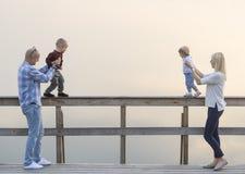 Счастливая семья 2 родителей и детей, одного мальчиков, ребёнок, имеет полезного время работы на моле реки Заход солнца Стоковое Изображение