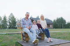 Счастливая семья 2 родителей и детей, одного мальчиков, ребёнок, сидя совместно снаружи Стоковое фото RF