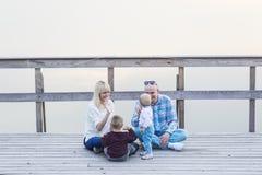 Счастливая семья 2 родителей и детей, одного мальчиков, ребёнок, сидя совместно на моле реки Стоковое Фото